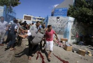 Palestinians carry a wounded man following what witnesses said was an Israeli air strike at a U.N.-run school in Rafah