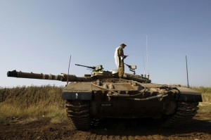 An Israeli soldier prays atop a tank close to the ceasefire line between Israel and Syria on the Israeli occupied Golan Heights