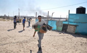 Palestinian man carries the body of a boy, whom medics said was killed by a shell fired by an Israeli naval gunboat, on a beach in Gaza City
